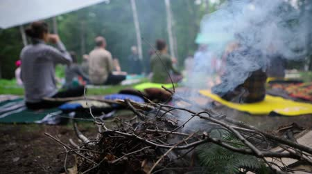 istenség : Slow motion footage of a smoldering camp fire as a group of individuals practice sacred and mindful yoga in a forest clearing during a multicultural celebration.