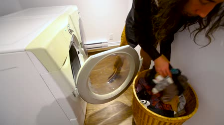 prát : Man with long hair putting dirty laundry in the washing machine in the utility room - fixed angle Dostupné videozáznamy