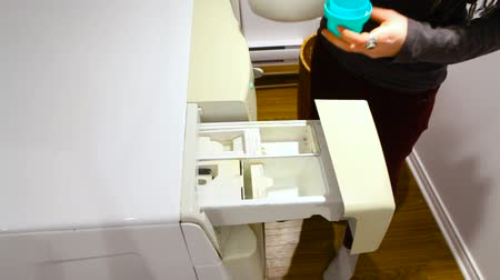 Young woman is putting dirty laundry in the washing machine and adding soap from the bottle, in the utility room - fixed angle Stock Footage