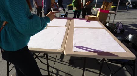 gösterici : an activist is preparing to paint placards on the morning of the environmental protest. Sheets of card board are taped to folding tables