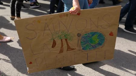 gösterici : Marching with a crowd of demonstrators at a peaceful environmental protest. One activist is carrying a placard that says save the planet in french