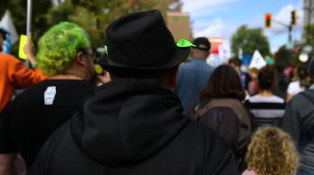 activist : Environmentalists marching at a peaceful demonstration viewed from the back with selective focus and a green theme, including green hair and scarf