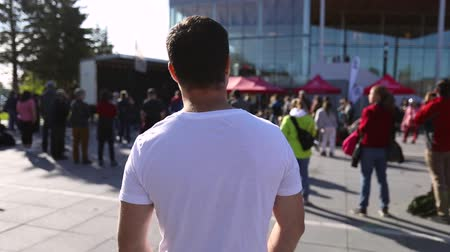 gösterici : A young man is seen from the back in white t shirt with selective focus. He watches an environmental protest outside a public building Stok Video