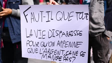 bastante : two close up shots of environmental slogans on hand written placards at a climate demonstration in french language