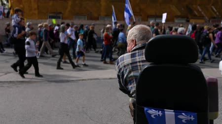 canadense : A disabled elderly man in a wheelchair viewed from the back watches marchers pass by at an environment demonstration in French Canadian City