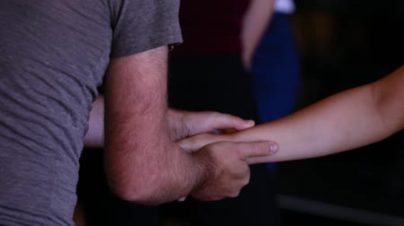 esfregar : Indoor dance festival workshop. Close up of wrist and hand massage by male dance instructor on a female dance student