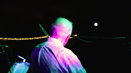 informal : Gray haired male violinist from back view performing on stage under colored lights with black background and copy space Stock Footage