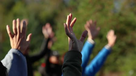 gestos : A group of people are exercising in a park. Seen is a close up of a group of hands slowly waving in the air with selective focus and beautiful light
