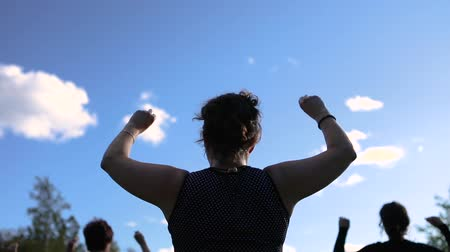 female hands : Outdoor dance festival workshop. A group of women exercising dramatically raise their arms in the air then lower their arms against a blue sky Stock Footage