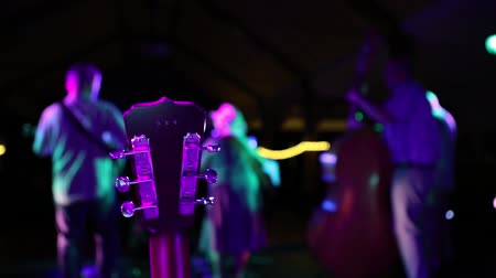 dvojitý : A country and western swing band perform on a stage with colored lights seen in selective focus from the back. An old guitar is in the foreground Dostupné videozáznamy