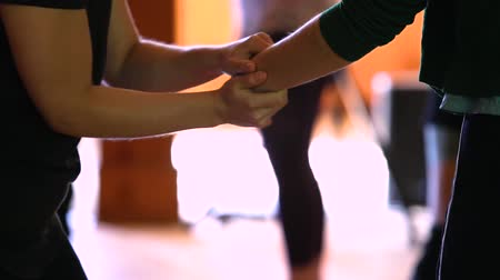 esfregar : Dance festival workshop. A close up of a dancer helping with stretching and massaging the arm and wrist of another dancer in rhythm Stock Footage