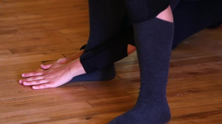 manipulace : Indoor dance workshop. Close up of hands and feet as one dancer gives other dancer an intense foot massage as she stands on a wooden floor