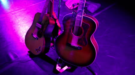batida : Acoustic guitars of dreadnaught and Southern Jumbo styles and a mandolin on guitar stands under violet colored light on stage before a show.