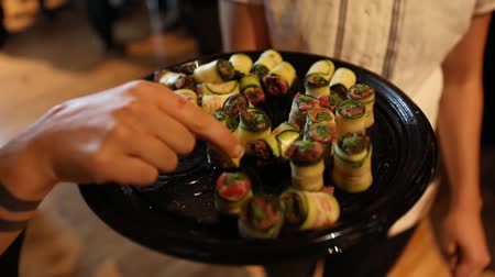 стартер : Close up shot of a tray of finger food, sliced cucumber with various fillings is offered around. It is filmed with selective focus and in slow motion