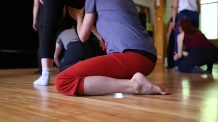 seletivo : Dance students kneeling on the floor and massaging the legs of other student standing in front of them. Clip is from low angle of view in slow motion