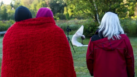 escaping : Three people watch a dance performance. It is cold and two people have a red blanket around them. The performance is a creation story.