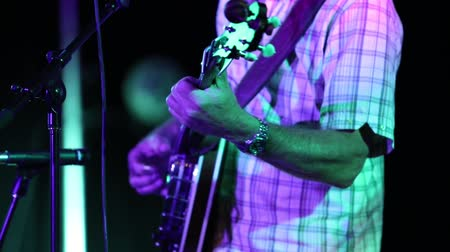 string instrument : A man in a checkered shirt is playing the banjo on a stage. He is under violet light and playing with a band filmed in slow motion