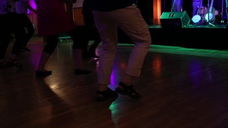 pessoal : Seniors in smart casual clothes are line dancing in the hall before the show begins. Musicians are setting up. Clip is from a low angle in slow motion