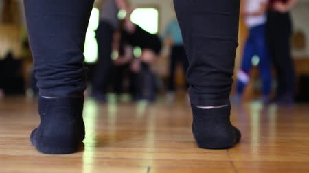 iluminado para trás : Dance movements seen from between the legs and feet of a dancer standing on the studio floor with selective focus from low angle Stock Footage