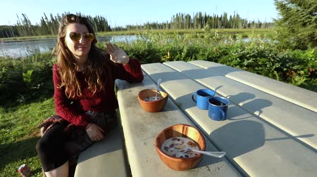 Çingene : view of outdoor breakfast table setting with coffee and muesli by the river. Woman in warm clothes sits in the sun at the table waving to the camera
