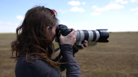 захват : A female photographer uses a professional camera and telephoto lens to capture the landscape. She stands in a field and snapping photos in slow motion Стоковые видеозаписи