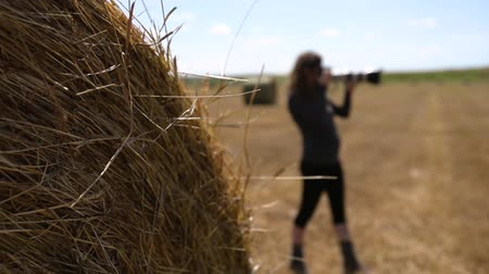 hay fields : Female photographer standing behind a haystack in sun, scanning the landscape with her camera. She is seen in profile, slow motion and selective focus