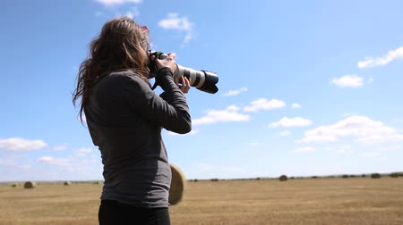 szénaboglya : A female photographer stands in a field. She looks through a telephoto lens to frame the landscape and is seen in slow motion from a low angle of view Stock mozgókép