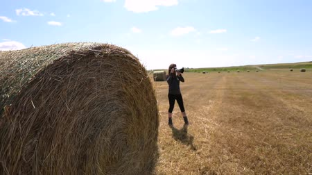 szénaboglya : female photographer shooting a haystack in sun. She scans the landscape with her camera. She is seen in slow motion with selective focus.
