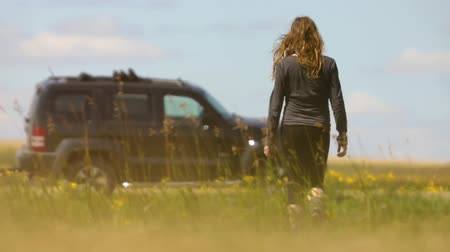 zaparkoval : A young woman walks away from camera through a field of tall grass towards a modern SUV parked by the road. Clip is in slow motion from a low angle