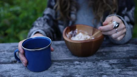 Çingene : Woman eating breakfast outdoors in early morning. She warms her hand on her coffee cup while eating her muesli from a wooden bowl. Stok Video
