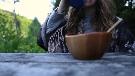 Çingene : Woman eating breakfast outdoors in early morning. She picks up coffee and drinks while eating her muesli from a wooden bowl in slow motion from low