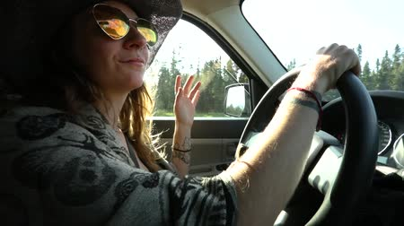 Çingene : Woman with cowboy hat, sunglasses, tattoos and long wavy brown hair is driving on a country road and dancing to music in slow motion looking to camera Stok Video