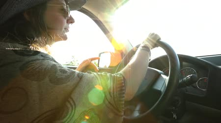 Çingene : Woman with cowboy hat, sunglasses, tattoos and wavy brown hair is driving on a country road and moving to music in slow motion with colored lens flare