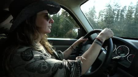 delici : Alternative woman with cowboy hat, sunglasses, tattoos and long wavy brown hair is driving on a country road seen in profile in slow motion Stok Video