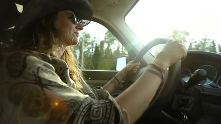 Çingene : Woman with cowboy hat, heart shaped sunglasses, tattoos and wavy hair drives on a road with strong light and lens flare. She looks to camera and cheers