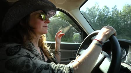 Çingene : Alternative woman with cowboy hat, sunglasses, tattoos and long wavy brown hair is driving on a country road and dancing to music in slow motion Stok Video