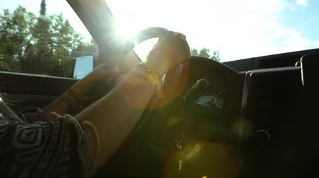 Çingene : Woman driving with hands on wheel with tattoos from low angle. Sun and lens flare comes through the windscreen creating dramatic light effect