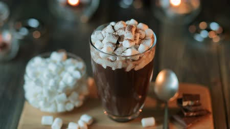 mályvacukor : Beautiful composition - hot chocolate with marmalade and chocolate pieces in a transparent glass. The glass stands on a wooden stand. Behind the candles are burning