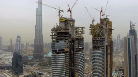dach : aerial view of several skyscrapers under construction with scaffolding and cranes. Dubai, UAE