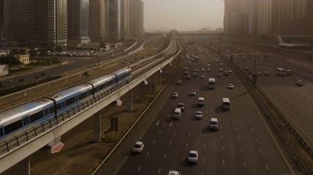 prospective : Aerial view of high-speed trains blue, which travels through the overpass along the highway with cars surrounded by skyscrapers. Dubai, UAE