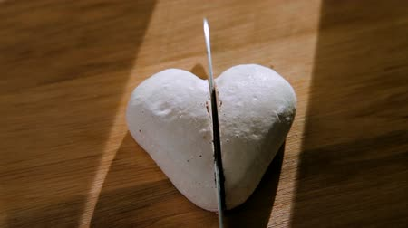 sentiment : the knife cuts white cookies in the shape of a heart into two halves