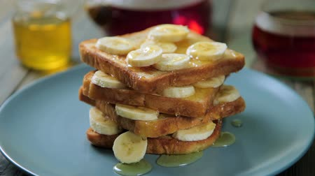 szirup : Fresh homemade crispy toast with honey and bananas on blue plate. Delicious breakfast. Stock mozgókép
