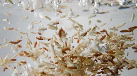 brown and red rice grain fall into boiling water. Macro view Stock Footage