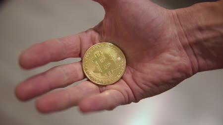 Male hand showing a gold coin Bitcoin on a brown background