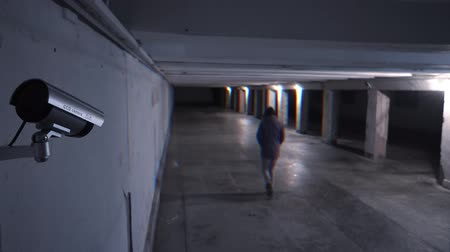 Kind of dangerous person walking at night on an underground passage in the background of a surveillance camera