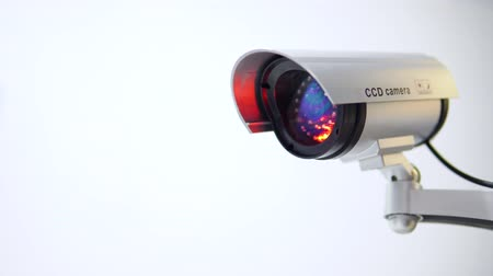 The surveillance camera with flashing red light on white background. Close up