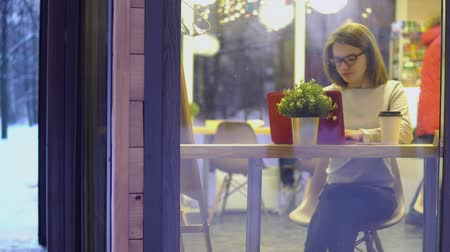 Young girl in a white sweater and wearing glasses, working on a red laptop in a cafe. View through the window.