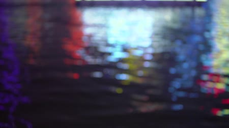 Blurred city lights with bokeh effect reflected on water Stock Footage