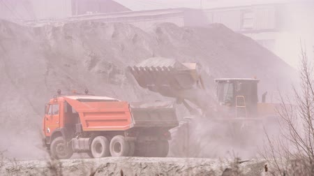 Excavator loading dumper truck with sand at a sand quarry Stock Footage