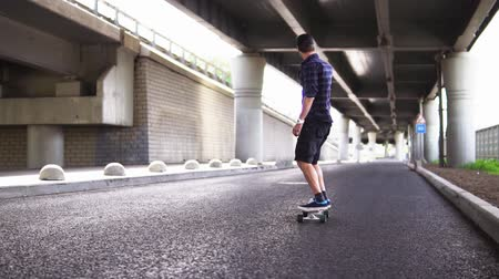 longboard : A man riding a skateboard on the asphalt on the background of the overpass